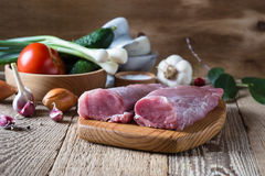 Raw pork tenderloin and vegetables on rustic wooden table. Raw pork tenderloin, tender  fillet  and vegetables on rustic wooden table Stock Image