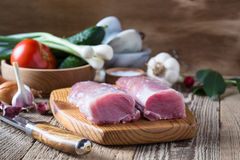 Raw pork tenderloin and vegetables on rustic wooden table. Raw pork tenderloin, tender  fillet  and vegetables on rustic wooden table Royalty Free Stock Photos