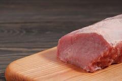 Raw pork tenderloin on a wooden cutting board on a dark background. Raw pork tenderloin on a cutting board on a dark background Royalty Free Stock Image