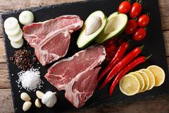 Raw porterhouse beef steak with ingredients close-up. Horizontal. Raw porterhouse beef steak with ingredients close-up on the table. Horizontal top view from Stock Photography