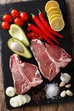 Raw porterhouse beef steak with ingredients close-up. Vertical t. Raw porterhouse beef steak with ingredients close-up on the table. Vertical top view from above Royalty Free Stock Photo