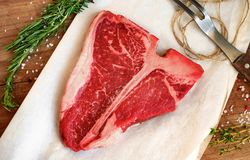 Raw porterhouse steak with herbs on a wooden Board. Raw porterhouse steak with herbs and salt is on the paper on a wooden Board Stock Images