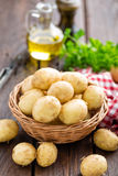Raw potato in basket on wooden table Royalty Free Stock Image