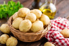 Raw potato in basket on wooden table Royalty Free Stock Images