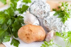 Raw potato close up and the potatoes in foil Royalty Free Stock Images