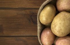 Harvest potatoes in burlap sack on wooden background Royalty Free Stock Photo