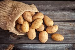 Raw potato food . Fresh potatoes in an old sack on wooden background. Top view Stock Photo