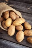 Raw potato food . Fresh potatoes in an old sack on wooden background. Top view Royalty Free Stock Photos