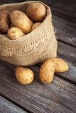 Raw potato food . Fresh potatoes in an old sack on wooden background. Top view Royalty Free Stock Photography