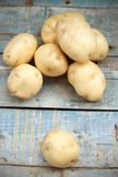 Raw potato. Heap of fresh raw potato on a wooden surface Royalty Free Stock Photography