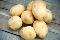 Raw potato. Heap of fresh raw potato on a wooden surface Stock Photography