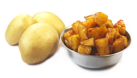 Raw potato and Potato Fry. Raw potato and Fresh South Indian potato fry in a bowl on isolated white background Royalty Free Stock Photography