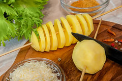 Raw potato spiral cut skewers with cheese, garlic, provanskiy herbs and green salad. Royalty Free Stock Images