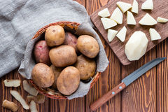 Raw potatoes in the basket, and peeled potatoes Stock Images