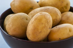 Raw potatoes in bowl Stock Photo