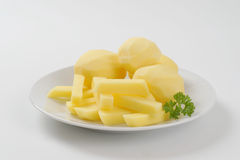 Raw potatoes and french fries. Plate of raw potatoes and french fries on white background Royalty Free Stock Image