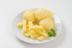 Raw potatoes and french fries. Plate of raw potatoes and french fries on white background Stock Photo