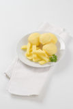 Raw potatoes and french fries. Plate of raw potatoes and french fries on white place mat Stock Photos