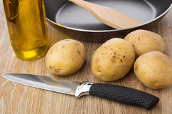 Raw potatoes, frying pan, vegetable oil and knife on table Royalty Free Stock Images