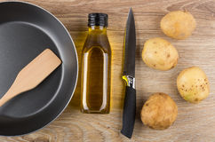 Raw potatoes, frying pan, vegetable oil and knife on table Stock Photos