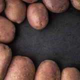 Raw potatoes at the left of the black stone table square Royalty Free Stock Photos