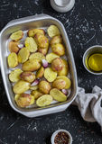 Raw potatoes with olive oil and spices in the baking dish. The preparation of baked potatoes. Royalty Free Stock Images