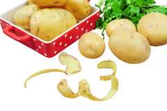 Raw potatoes and peels, isolated Stock Images