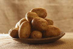 Raw potatoes on plate with burlap rustic royalty free stock image