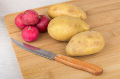 Raw potatoes, radishes and knife on wooden board. Raw potatoes, radishes and knife on wooden kitchen board Royalty Free Stock Image