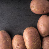 Raw potatoes at the  right of the black stone table square Royalty Free Stock Photo