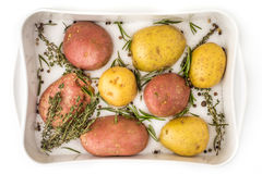 Raw potatoes with spices and herbs in the backing dish top view Stock Photo