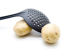 Raw Potatoes With Skimmer Stock Images