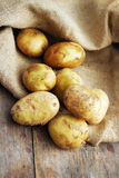 Raw potatoes on wooden background. With burlap Stock Photo