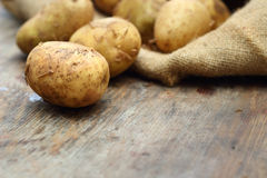 Raw potatoes on wooden background. Copy space Royalty Free Stock Images