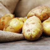 Raw potatoes on wooden background. Fresh vegetables Royalty Free Stock Photography