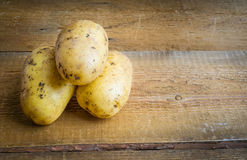 Raw potatoes on wooden background. Raw uncooked potatoes on wooden background with copy space Stock Photo
