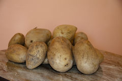 Raw potatoes. On wooden table Royalty Free Stock Photography