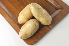 Raw potatoes on wooden tray. Close up of raw potatoes on wooden tray Stock Images