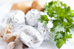 Raw potatoes wrapped in foil Royalty Free Stock Photography