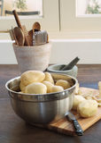 Raw potatos in kitchen scene Royalty Free Stock Image