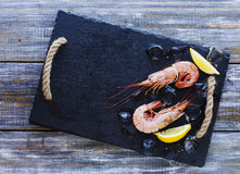 Raw prawns with lemon and ice, selective focus Stock Images