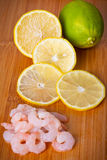 Raw prawns with lemon slices and lime Royalty Free Stock Images