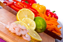 Raw prawns with lemon slices and lime Stock Photo