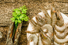 Raw prawns rustic table. Raw prawns in a plate old wooden table Royalty Free Stock Photography