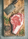 Raw prime beef meat dry-aged steak rib-eye and chopping knife. Flat-lay of raw prime beef meat dry-aged steak rib-eye on bone and chopping knife on wooden board Royalty Free Stock Photography