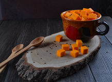 Raw pumpkin cut cubes in a cup. Vegetarian food. Raw pumpkin cut cubes in a cup ,wooden spoon  on dark wooden background Royalty Free Stock Photo