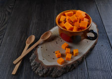Raw pumpkin cut cubes in a. Vegetarian food. Raw pumpkin cut cubes in a cup ,wooden spoon  on dark wooden background Royalty Free Stock Photos