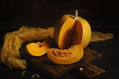 Raw pumpkin cut into pieces on a dark background. Raw pumpkin cut into pieces on a dark background Stock Photo