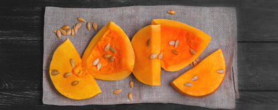 Raw pumpkin pieces cut for baked. Halloween raw pumpkin pieces cut for baked, napkin tissue, pumpkin seeds on dark black background, top view Stock Images