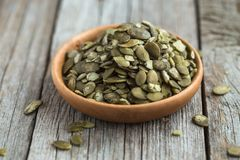 Raw Pumpkin seeds close up in wooden bowl stock photo